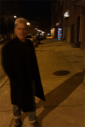 Jim Cory, poet, on night street with long shadow